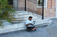 Mexican man with deformed legs and feet sitting on a skateboard and reading a newspaper, Cancun, Quintana Roo, Mexico