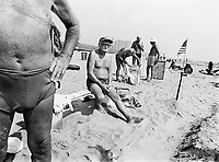 "USA. New York City. A group of old men with swimsuits are resting on the sandy beach in Coney Island. Towel with a penguin. An american flag. The national flag of the United States of America, often simply referred to as the American flag, consists of thirteen equal horizontal stripes of red (top and bottom) alternating with white, with a blue rectangle in the canton (referred to specifically as the ""union"") bearing fifty small, white, five-pointed stars arranged in nine offset horizontal rows of six stars (top and bottom) alternating with rows of five stars. The 50 stars on the flag represent the 50 states of the United States of America and the 13 stripes represent the thirteen British colonies that declared independence from the Kingdom of Great Britain and became the first states in the Union. Nicknames for the flag include the ""Stars and Stripes"", ""Old Glory"", and ""The Star-Spangled Banner"". © 1985 Didier Ruef"