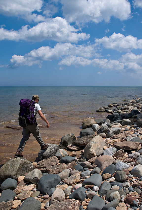 A backpacker hikes a cobblestone beach near Au Sable Point in Pictured Rocks National Lakeshore near Grand Marais, Mich.