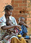 A woman and her children take a break to eat at an agricultural school sponsored by the United Methodist Committee on Relief (UMCOR) in Kaminsamba, Democratic Republic of the Congo. Participants, some of whom stay at the center for several weeks, learn sustainable agricultural practices, animal traction, and beekeeping.