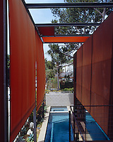 A steel framework above the lap pool supports orange and yellow fabric blinds that move in all directions