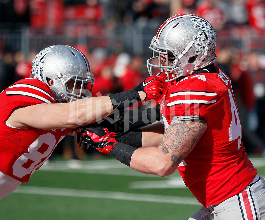 Ohio State Buckeyes defensive lineman Chris Rock (44) warms up with Ohio State Buckeyes tight end Jeff Heuerman (86) during the first quarter of the NCAA football game against Michigan at Ohio Stadium on Saturday, November 29, 2014. (Columbus Dispatch photo by Jonathan Quilter)