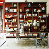 A wall of Chinese-style shelves at one end of the living room displays a collection of blue and white bowls and urns alongside the books