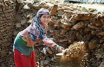 Anita Shakya cleans up rubble in Dhawa, a village in the Gorkha District of Nepal.