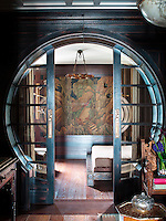 Circular sliding doors in the entrance hall create a visual tunnel leading the eye to an Art Deco panel on the wall beyond