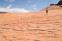 Person walking in distance on textured red sandstone above lake Powell