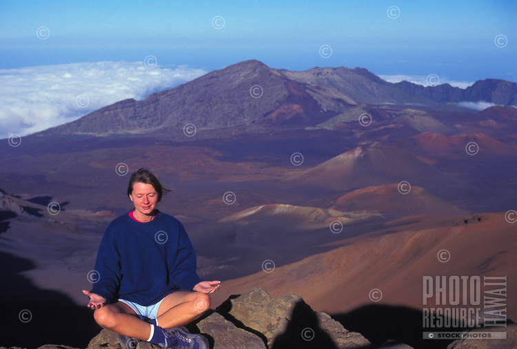 Woman meditating at the crater of Haleakala National Park, house of the sun, Maui
