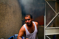Baghdad, Iraq, April 14, 2003.A man tries to put out a fire in his house in Saddam city after an Iraqi hidden artillery depot exploded, levelling 4 houses and projecting shells and debris at several hundred meters. Several other houses caught fire in the incident...