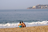 Couple watching waves crash onto the beach in Acapulco, Mexico