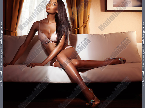Beautiful glamorous sexy black woman in pink lingerie sitting on a white sofa in a dimly lit room, glamour photo.