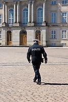 Policeman in Copenhagen, Denmark walking across the square at Amalienborg Palace.