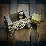 Vintage porcelain doll and wooden train resting on antique trunk