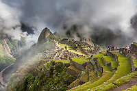 Morning fog and clouds reveal Machu Picchu, the ancient &quot;lost city of the Incas&quot;, 1400 CA, 2400 meters. Discovered by Hiram Bingham in 1911. One of Peru's top tourist destinations. Urubamba river in the distance.