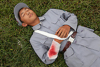 A competitor dressed in a PLA (People's Liberation Army) revolutionary era outfit lies 'wounded' on the 'battlefield' waiting to be picked up in the 'Rescue the Wounded Soldier' event of the Red Games. Held in Junan County, this sporting event is a nostalgic tribute to the communist era.