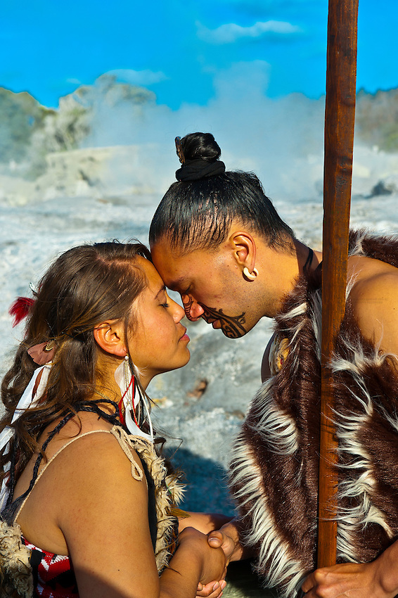 A Maori man with ta moko (facial tattoo) and woman doing hongi (traditional Maori greeting) with the Pohutu Geyser behind, Te Puia (New Zealand Maori Arts & Crafts Institute), Rotorua, New Zealand