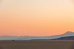 A family experiences the serene soft orange and red light after sunset in the Alvord Desert in a remote part of Southeast Oregon while overland camping with a rooftop tent.