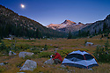 Backpacking camper in Lostine River valley meadow with moon rising over Eagle Cap mountain; Eagle Cap Wilderness, Wallowa Mountains, Oregon.