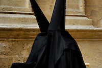 The Holy Week participants wearing a black tunic and a hood with the conical hat (capirote) passing in front of the Cathedral during the Easter celebration in Malaga, Spain, 2 April 2007.