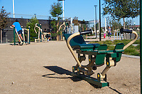 Bodyweight based exercise equipment is used by two women at Stanton Central Park, with a woman and child in the distance.