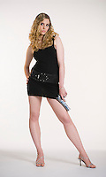 Caucasian blonde woman posing towards camera holding handgun on white seamless