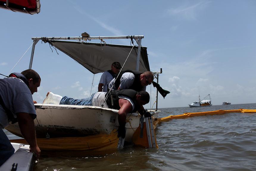 Delacroix Island fishermen working for St Bernard Parish collect 209 bags of absorbent boom around Black Bay, LA on July 19, 2010.