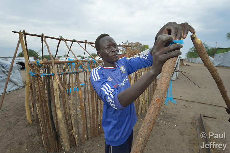 Galuak Kuon works on his home on April 15, 2017, in Poktap, a town in South Sudan's Jonglei State where conflict, drought and inflation have caused severe food insecurity. Like most here, he fled Poktap in 2013 when South Sudan's civil war broke out, and just returned in January 2017. <br /> <br /> The blue fabric used to fasten many of the sticks together is torn from insecticide-treated bednets, which villagers have discovered provide a termite-resistant material for construction.<br /> <br /> The Lutheran World Federation, a member of the ACT Alliance, is helping families in the area tackle food problems, including with the provision of cash for the purchase of fishing line and hooks, as well as assisting with home construction.