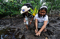 Bapak Juanda Datundugon with a member of the village mangrove working group helping to plant seedlings, Dudepo, Bolmong Selatan, Sulawesi, Indonesia.