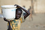 A displaced boy carries water home in a bucket in Agok, a town in the contested Abyei region where tens of thousands of people fled in 2011 after an attack by soldiers and militias from the northern Republic of Sudan on most parts of Abyei. Although the 2005 Comprehensive Peace Agreement called for residents of Abyei--which sits on the border between Sudan and South Sudan--to hold a referendum on whether they wanted to align with the north or the newly independent South Sudan, the government in Khartoum and northern-backed Misseriya nomads, excluded from voting as they only live part of the year in Abyei, blocked the vote and attacked the majority Dinka Ngok population. The African Union has proposed a new peace plan, including a referendum to be held in October 2013, but it has been rejected by the Misseriya and Khartoum. The Catholic parish of Abyei, with support from Caritas South Sudan and other international church partners, has maintained its pastoral presence among the displaced and assisted them with food, shelter, and other relief supplies.