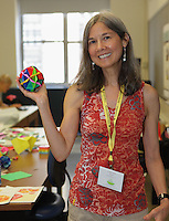 New York, NY, USA - June 23, 2012: Lottie Wolff, from Connecticut, in a classroom where she is teaching a modular Origami model called Borealis designed by David Petty, to attendees at the annual OrigamiUSA 2012 convention held at Fashion Institute of Technology in New York City. Experts teach classes of students how to fold the various Origami designs, from simple to highly complex.