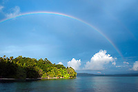 Raja Ampat Archipelago, West Papua, Indonesia, December 2010. A rainbow brings good luck after the daily thunderstorm. Thousands of small islands fringed by coral reefs and blue water mangroves litter the Raja Ampat archipelago. The turquoise and blue waters are teeming with marine life that forms the livelihood for the local Papuan population. The Raja Ampat Research & Conservation Centre (RARCC) supports the locals to develop a community based, sustainable tourism project, inviting visitors to explore their islands by sea kayak and experience the culture by staying amongst the local people in traditional style homestays. Photo by Frits Meyst/Adventure4ever.com
