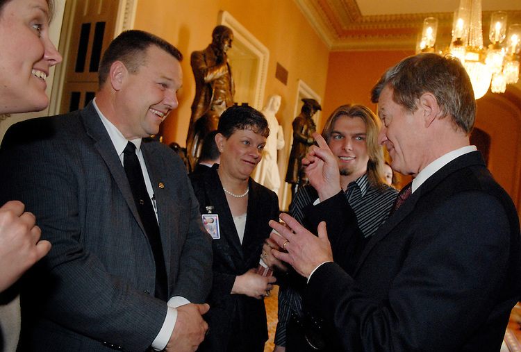 Sen. Jon Tester, D-Mont., talks with Sen. Max Baucus, D-Mont., after a mock swear-in ceremony in the Old Senate Chamber.  Tester's wife Sharla and son Shon, appear between them.