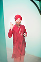 Man wearing a red turban and Indian shirt gesturing with spiritual mudras.