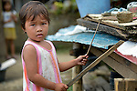 Stephanie Fortaleza, 4, plays music by beating on sheets of rusty tin roofing that are piled up following the November 2013 passage of Typhoon Haiyan through her neighborhood in Ormoc, a city in the Philippines province of Leyte. The storm was known locally as Yolanda. Lutheran World Relief and other ACT Alliance members have been providing a variety of forms of assistance to survivors here, including an LWR-sponsored cash for work program that has allowed residents to recover more quickly.
