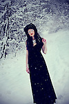A pale girl wearing a long black gown stanidng in a snowy forest..