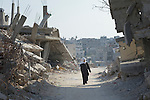 A woman walks through Shejaiya, a Gaza neighborhood which bore the brunt of some of the most intense Israeli air attacks during the 2014 war. Throughout Gaza, members of the ACT Alliance are supporting health care, vocational training, rehabilitation of housing and water systems, psycho-social care, and a variety of other humanitarian activities.