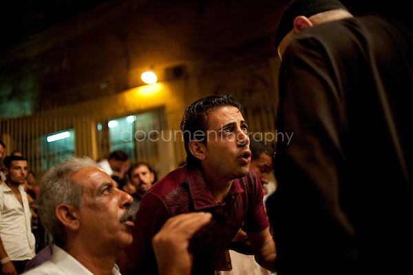 A devoted Copt implores Father Samaan to take a moment to bless him. <br /> <br /> copyright : Magali Corouge / Documentography