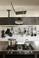 A variety of kitchen utensils hangs from a chrome rail above the marble splashback in the kitchen