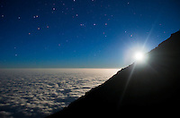 Tanzania - Full moon sets over a roof of clouds. Mt. Kilimanjaro, Tanzania