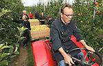 Foto: VidiPhoto<br /> <br /> RESSEN - Onder toezicht van fruitteler Nico van Olst uit het Betuwse Ressen, mogen de bakkers van Droom -een horecaonderneming voor mensen met een beperking- woensdag de eerste appels van het seizoen plukken. De zomerappel Delbare Estival, is volgens Van Olst de lekkerste appel van het seizoen en uitermate geschikt voor appeltaarten. Daar moesten de bakkers van Droom meer van weten en met het hele team kwamen ze woensdag opdraven om de fruitbaas een handje te helpen en om als eerste de verse oogst in de wacht te slepen. Droom, met zo'n 50 werknemers, is onderdeel van Stichting de Driestroom voor mensen met een handicap en is actief op horecagebied. De bakkerij bakt zo'n 200 appeltaarten per week, die vervolgens bij diverse horecagelegenheden verkocht worden. Fruitteeltbedrijf De Woerdt van de familie Van Olst telt zo'n 20 ha. hard fruit (appels en peren) en bezit een van de grootste landwinkels van ons land.