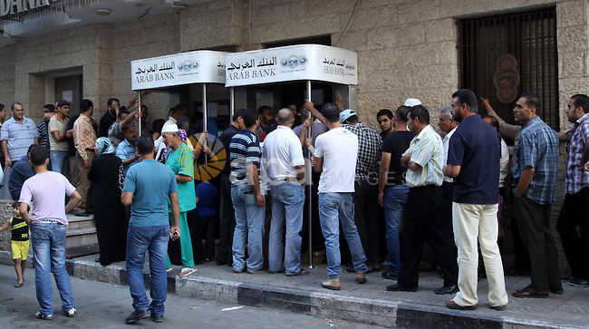 Palestinian Authority civil servants gather outside the Arab Bank in Gaza city on Oct. 04,2011, to withdraw their monthly salaries. Photo by Mohammed Asad