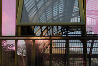 New Caledonia Glasshouse (formerly The Mexican Hothouse), 1830s, Charles Rohault de Fleury, Jardin des Plantes, Museum National d'Histoire Naturelle, Paris, France. Low angle view through the glass structure of the glasshouse, the glass windows reflecting the late afternoon light and the silhouettes of the trees of the Jardin des Plantes. Through a semi-opened window the glass and metal roof structure appears lit by the sunset. In the distance the Tropical Rainforest Glasshouse may be seen. The New Caledonia Glasshouse, or Hothouse, was the first French glass and iron building.
