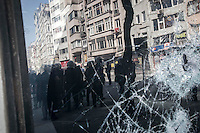 n this Tusday, Jun. 11, 2013 photo, anti-riot police are seen reflected in a crashed window during clashes at the streets of Taksim Square in Istanbul,Turkey. (Photo/Narciso Contreras).