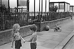 Children playing together in the street, south London prefab housing behind them. England 1970s...