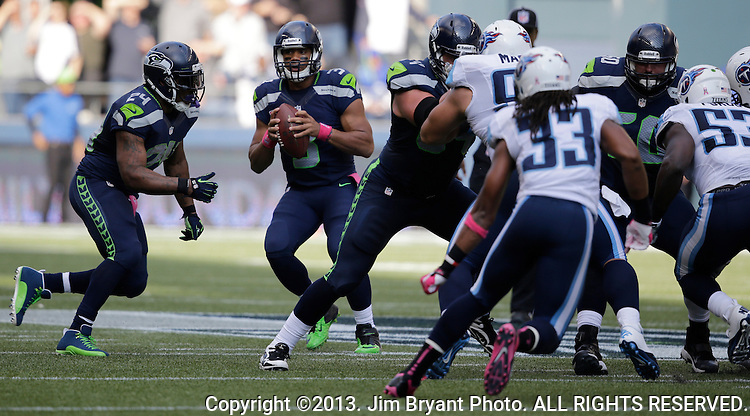 Seattle Seahawks quarterback Russell Wilson looks to pass against the Tennessee Titians at CenturyLink Field in Seattle, Washington on  October 13, 2013. The Seattle Seahawks beat the Titians  20-13.   ©2013. Jim Bryant Photo. All Rights Reserved.