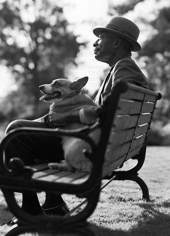 An elderly african-american man sits on a park bench with his dog on his lap