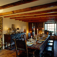 The candlelit dining table is covered with a tartan blanket which acts as a table cloth