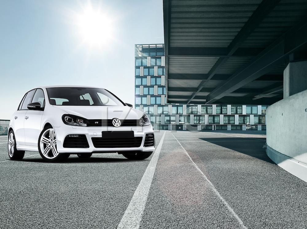 One white 2011 Volkswagen Golf R-Line Hatchback parked outdoors near modern architecture.