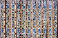 Painted wooden ceiling with floral, vegetal and interlacing designs, from the gallery of the central courtyard area, in a typical Tetouan riad, a traditional muslim house built around a courtyard, built in Moorish style with strong Andalusian influences, next to the Great Mosque or Jamaa el Kebir in the Medina or old town of Tetouan, on the slopes of Jbel Dersa in the Rif mountains of Northern Morocco. Tetouan was of particular importance in the Islamic period from the 8th century, when it served as the main point of contact between Morocco and Andalusia. After the Reconquest, the town was rebuilt by Andalusian refugees who had been expelled by the Spanish. The medina of Tetouan dates to the 16th century and was declared a UNESCO World Heritage Site in 1997. Picture by Manuel Cohen