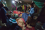 In the mountain village of Marpak, in Nepal's Dhading District, Preeta Tamang, 13, puts on her school uniform at 5:30 am, well before sunrise, as her sister Ritu, 14, looks on. The rest of their family remained asleep. The girls started class at 6 am. Their family's home was destroyed in Nepal's 2015 earthquake.