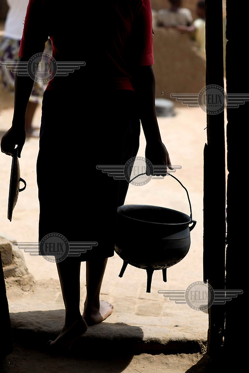 24 year old Sithokozilg takes a pot outside to cook maize over a fire...
